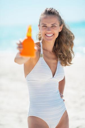 sun screen: Happy young woman showing sun screen creme