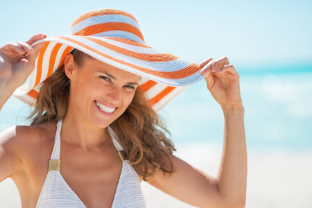 Portrait of smiling young woman in hat on beach photo