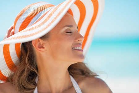 Portrait of relaxed young woman in hat on beach photo
