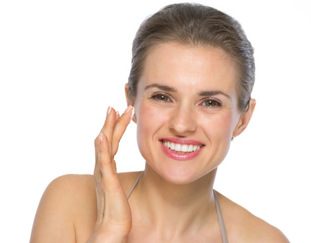 Portrait of happy young woman applying creme on face photo
