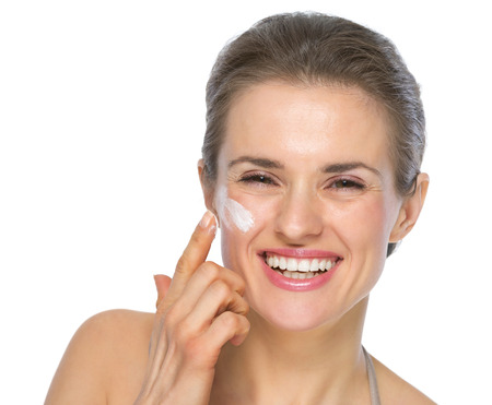 Happy young woman applying creme on face photo