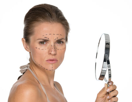 disquieted: Concerned young woman with plastic surgery marks and mirror