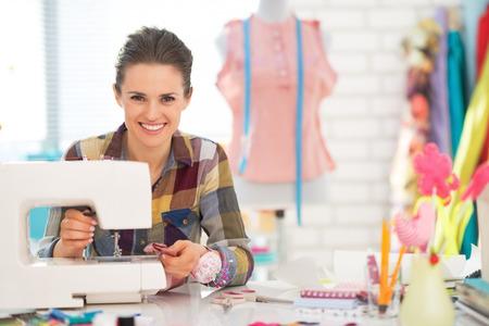 ミシン スタジオの幸せな女性の裁縫師 写真素材