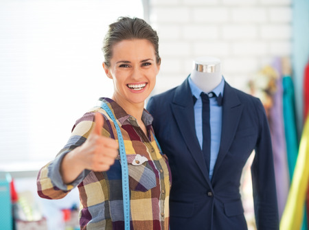 Happy seamstress near mannequin in suit showing thumbs up