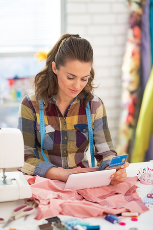 Seamstress with credit card using tablet pc