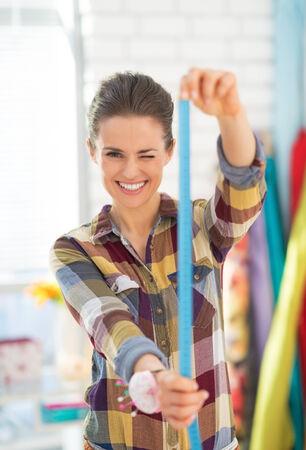 Happy seamstress using measuring tape