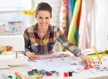 máquina de coser: Costurera feliz que trabaja en el estudio Foto de archivo