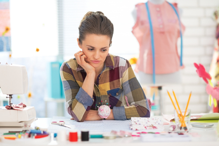 disquieted: Portrait of concerned seamstress in studio