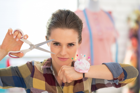 Portrait of confident seamstress with scissors and pincushion
