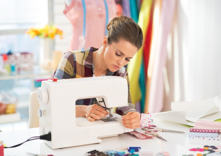 maquinas de coser: Costurera trabajando con la máquina de coser Foto de archivo