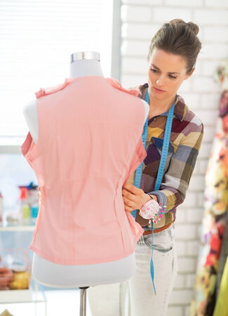 Seamstress adjusting clothing on mannequin photo