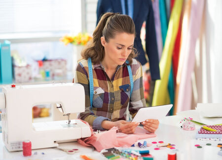 Seamstress using tablet pc at work Stock Photo - 28715916