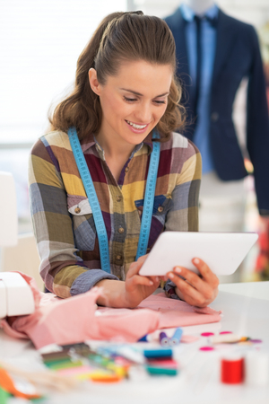 Happy seamstress using tablet pc at work Stock Photo - 28667980
