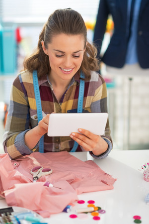Smiling seamstress using tablet pc at work Stock Photo - 28715917