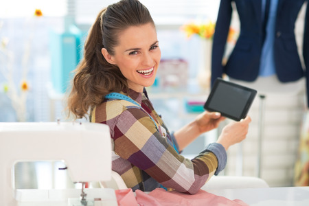 topicality: Happy seamstress using tablet pc at work