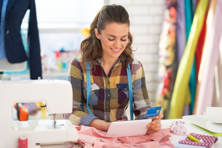 Seamstress with credit card using tablet pc Stock Photo - 28667984