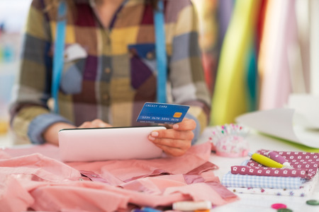 Closeup on seamstress with credit card using tablet pc Stock Photo - 28641126