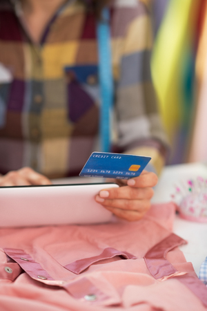 Closeup on seamstress with credit card using tablet pc Stock Photo - 28667985