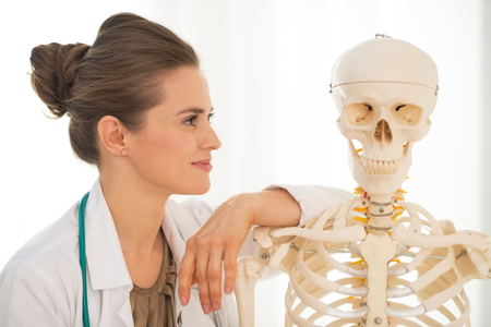 Portrait of medical doctor woman looking on human skeleton anatomical model photo
