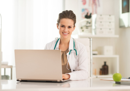 topicality: Happy medical doctor woman working on laptop Stock Photo