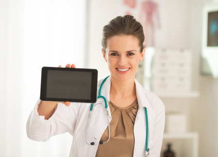 Happy medical doctor woman showing tablet pc blank screen Stock Photo
