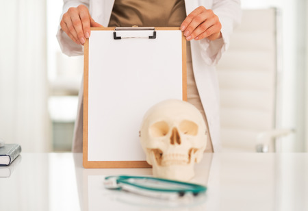Closeup on medical doctor woman showing blank clipboard photo