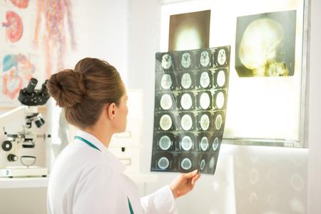 Mujer del médico que mira en la tomografía