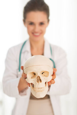 Closeup on medical doctor woman showing human skull photo