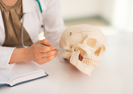 Closeup on medical doctor woman pointing on human skull photo