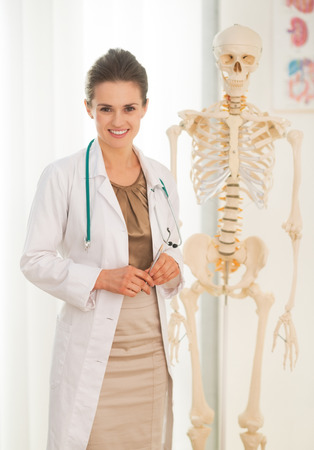 Portrait of happy medical doctor woman near human skeleton anatomical model photo