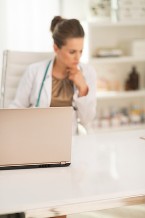 topicality: Closeup on laptop and thoughtful medical doctor woman in background