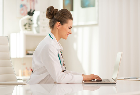 Medical doctor woman working on laptop in office