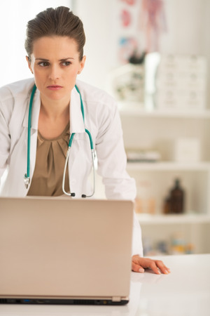 disquieted: Portrait of concerned medical doctor woman with laptop in office
