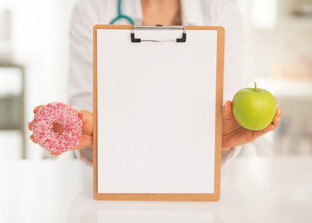 Closeup on medical doctor woman showing blank clipboard apple and donut photo