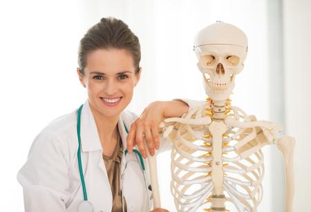 Portrait of smiling medical doctor woman near human skeleton anatomical model photo