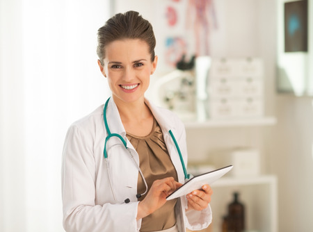 topicality: Smiling medical doctor woman using tablet pc