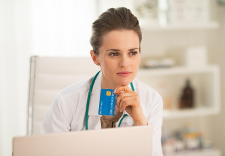 topicality: Portrait of thoughtful medical doctor woman credit card with and laptop