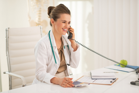 Happy medical doctor woman talking phone Stok Fotoğraf