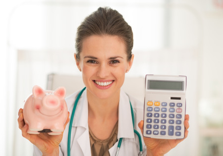 Portrait of happy medical doctor woman showing piggy bank and calculator photo