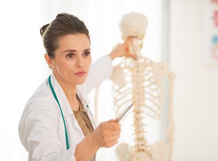 Medical doctor woman teaching anatomy using human skeleton model photo