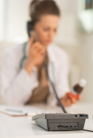 Closeup on medical doctor woman with medicine bottle talking phone Banco de Imagens