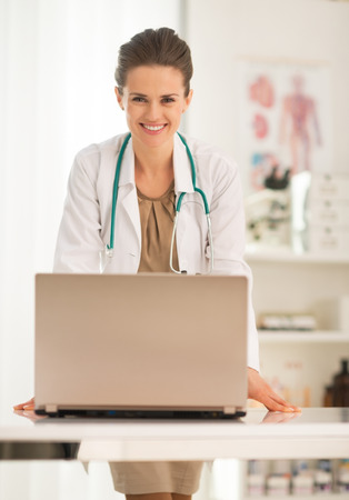 topicality: Portrait of happy medical doctor woman with laptop in office