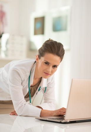 topicality: Portrait of medical doctor woman working on laptop in office