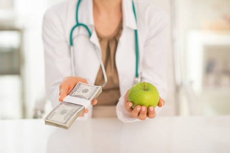 doctor holding money: Closeup on medical doctor woman holding apple and money pack in hands Stock Photo