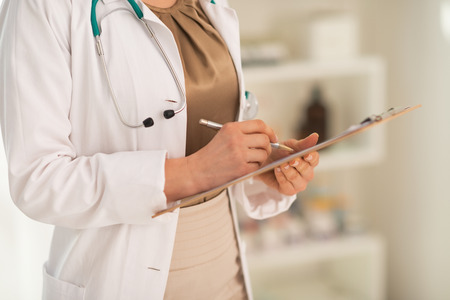 Closeup on medical doctor woman writing in clipboard Stock Photo - 28769579