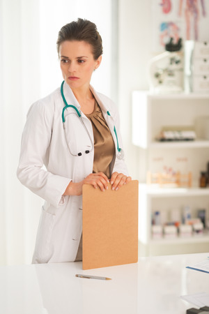Thoughtful medical doctor woman with clipboard Stock Photo - 28769580