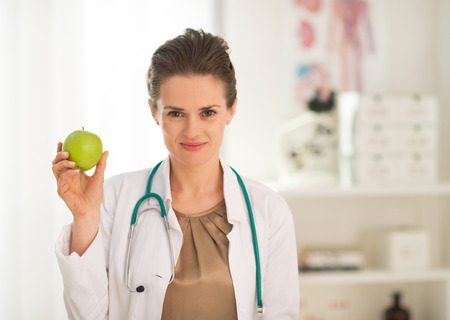 Medical doctor woman showing apple Stock Photo - 28769582