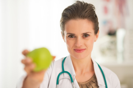 Medical doctor woman giving apple Stock Photo - 28769583