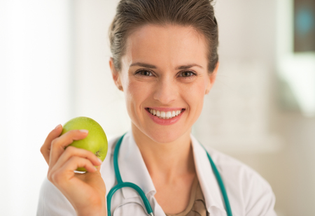 Portrait of smiling medical doctor woman with apple photo