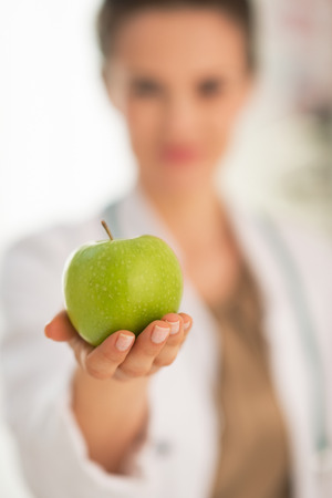 Closeup on medical doctor woman giving apple Stock Photo - 28769587